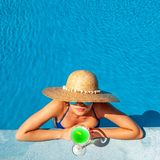 Woman at poolside with cocktail. Woman in hat relaxing at the pool with cocktail Stock Photos