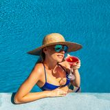Woman at poolside with cosmopolitan cocktail. Woman in hat relaxing at the pool with cosmopolitan cocktail Royalty Free Stock Photo