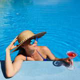 Woman at poolside with cosmopolitan cocktail Stock Photos