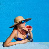 Woman at poolside with cosmopolitan cocktail Royalty Free Stock Photos