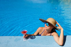 Woman at poolside with cosmopolitan cocktail Royalty Free Stock Images