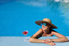 Woman at poolside with cosmopolitan cocktail Royalty Free Stock Image