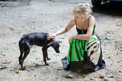 Woman with a poor stray dog Royalty Free Stock Image