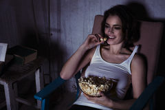 Woman with popcorn watching movie and laughing. Adult girl eating popcorn in delighted  living-room Stock Photography