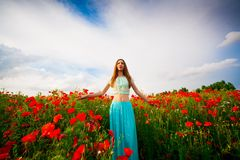 Woman poppies field, full height. Beautiful woman in the red flowers poppies. Has long hair, clothed turquoise blouse and shirt. Has sexy slim body. Portrait in Royalty Free Stock Images