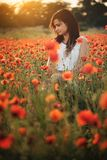 Woman on poppy field. Beautiful young girl on poppy field with dress stock photo