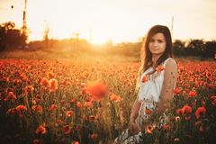 Woman on poppy field. Beautiful young girl on poppy field with dress stock photos