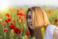 Woman in poppy field holding one poppy Stock Photos