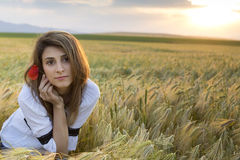 Woman with poppy flower. Young beautiful woman with poppy flower in wheat Field stock photo