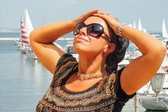 Woman in port. Caucasian brunette woman in marina against yachts in port Stock Image