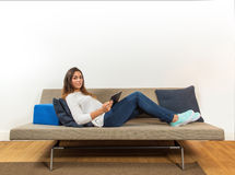 Woman with a portable tablet lying on a couch Royalty Free Stock Photo