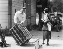 Woman and a porter carrying her trunk Stock Photos