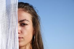 Woman portrait. Portrait of a young woman covering half of her face with a shawl stock images