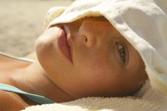 Woman portrait. A young woman is looking through a towel while taking a sunbath Stock Photography