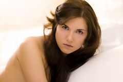 Woman portrait. Studio portrait of a beautiful undressed caucasian woman in bed staring with serious facial expression Stock Photos
