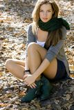 Woman portrait in autumn colors. Young brunette woman portrait in autumn colors. She's seating on the ground in autumn park Royalty Free Stock Image