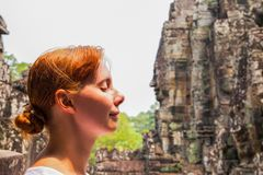 Woman portrait in Bayon temple, Siem Reap, Cambodia. Face of young woman and face of statue. Moderna and ancient concept. Meditating woman in Angkor temple Royalty Free Stock Image
