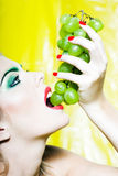 Woman Portrait bite grape. Beautiful woman portrait with colorful make-up  and background eating grape Royalty Free Stock Image