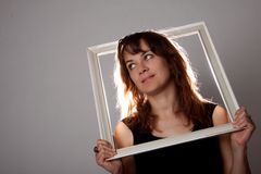 Woman portrait with frame. In a studio Royalty Free Stock Photography