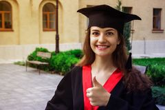 Woman portrait on her graduation day. thumbs up. University. Education, graduation and people concept.  royalty free stock photography