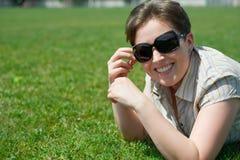 Woman portrait, lie on green grass, city park, summer outdoor Stock Image