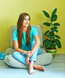 Woman portrait in living room sitting on a floor at pillows. Royalty Free Stock Photography