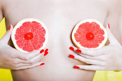 Woman Portrait Naked with Grapefruit breast. Caucasian woman naked with holding grapefruit breast studio on yellow background Stock Photography