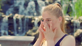 Woman portrait outdoor. Young woman posing near waterfall. Close up of blonde girl in sunlight. European woman portrait at summer. Woman looking away outdoor stock footage