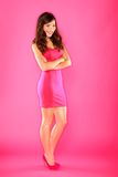 Woman portrait in pink. Beautiful smiling happy sexy full body portrait of pretty slender female fashion model in pink dress wearing pink high heels shoes on Stock Photo
