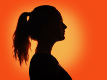 Woman portrait profile in silhouette shadow. On studio orange background royalty free stock photos