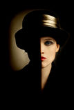Woman portrait retro hat. Woman face with black half. Artistic portrait of beautiful woman in black hat Stock Image