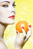 Woman portrait showing a orange tangerine fruit Royalty Free Stock Photos
