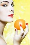 Woman portrait showing a orange tangerine fruit Royalty Free Stock Photos