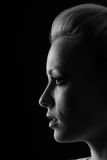 Woman portrait silhuette in darkness with soft light on face. Royalty Free Stock Images