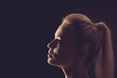 Woman portrait silhuette in darkness with soft light on face. Stock Photo