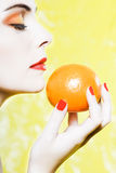 Woman portrait smelling an orange tangerine fruit. Beautiful caucasian woman portrait smelling an orange tangerine fruit  studio on yellow background Royalty Free Stock Image