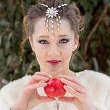 Woman Portrait, Snow Queen. Winter portrait of a young pretty woman holding a red apple, snow fairy makeup Stock Photography