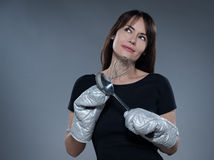 Woman Portrait thinking holding kitchen utensils Royalty Free Stock Images