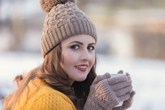Woman Portrait. Winter portrait of a young pretty woman, drinking a cup of coffee Royalty Free Stock Images