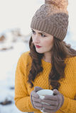Woman Portrait. Winter portrait of a young pretty woman drinking a cup of coffee Stock Photography
