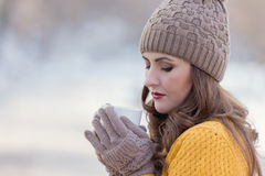 Woman Portrait. Winter portrait of a young pretty woman drinking a cup of coffee Royalty Free Stock Photography