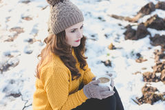 Woman Portrait. Winter portrait of a young pretty woman drinking a cup of coffee Royalty Free Stock Image