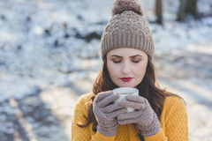 Woman Portrait. Winter portrait of a young pretty woman drinking a cup of tea Royalty Free Stock Photos