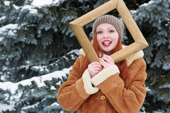 Woman portrait in wooden photo frame at winter season. Snowy weather in fir tree park. Stock Photos
