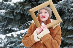 Woman portrait in wooden photo frame at winter season. Snowy weather in fir tree park. Royalty Free Stock Photo
