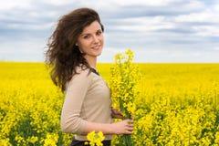 Woman portrait in yellow flower field Stock Image