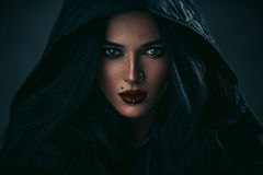 Woman portrait. Young sexy brunette woman with piercings portrait in hood. Dark dramatic colors Stock Image