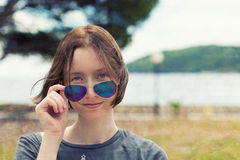 Woman Portrait. Portrait of young woman in sun glasses, with blurred sea landscape behind. Textured Royalty Free Stock Image