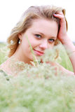 Woman portraits. Portrait of the young girl on the nature among grasses and smiling on the chamber Royalty Free Stock Photo