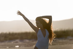 Woman pose at the beach. Photo taken with backlight Royalty Free Stock Image
